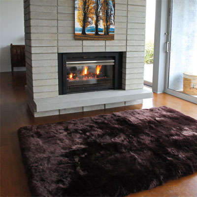 chocolate wool rug on a wooden floor in front of a fireplace