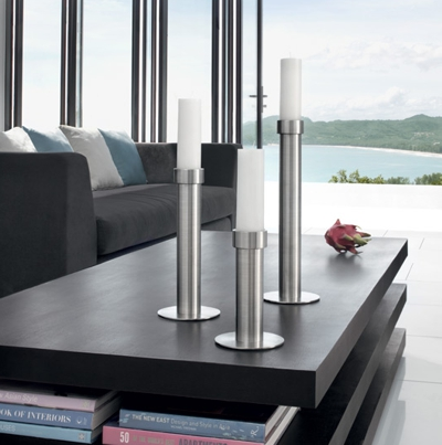 set of three stainless steel candlesticks of increasing height with white candles grouped on dark wood table